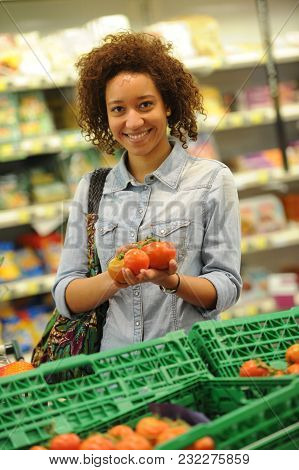 Woman Buys Vegetable And Food In The Supermarket