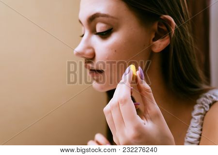 A Young Sleepy Girl Wants To Sleep, Inserts In Her Ears Yellow Earplugs Against Street Noise