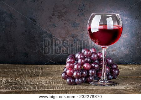 Wineglass With Red Wine And Red Grapes On Wooden Table. Dark Background.