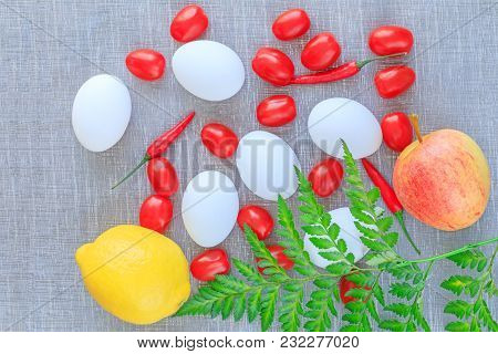 Easter Composition: Eggs, Tomatoes, Chilli Pepper, Apple And Lemon On The Textured Background. Veget