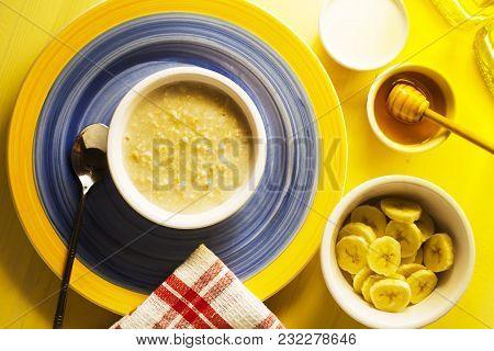 A Breakfast Table Of Organic Hot Porridge And Banana With Honey
