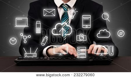 Businessman in suit typing with multimedia concept above
