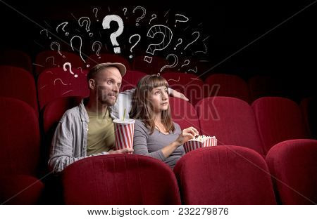 Nice couple in cinema with drawn question signs around