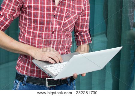Man In Casual Clothes Standing Working With Laptop. Student. Hipster. Freelancer. The Developer. Onl