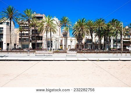 White Sand Beach With Train Station In Badalona, Costa Brava, Spain. Palms Trees, Hotel Buildings, A