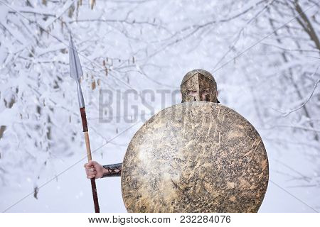 Warrior From Sparta Keeps Big Round Metallic Shield In One Hand And Sharp Spear In Another. He Has T