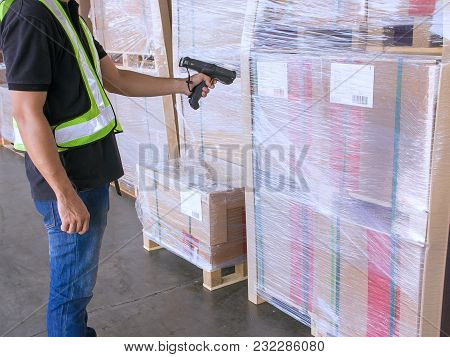 Warehouse Worker Holding Barcode Scanner With Scanning On A Pallet Of Product.
