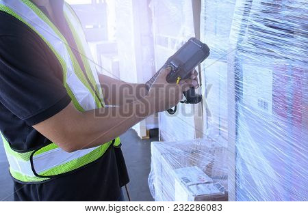 Warehouse Worker Hand Holding Barcode Scanner With Checking And Inventory Of A Products.
