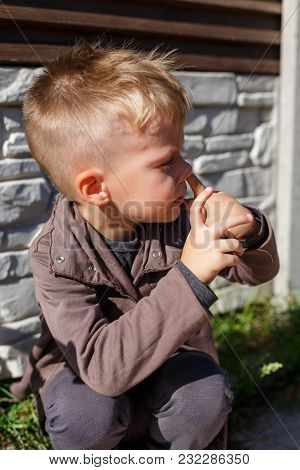 Beautiful Little Boy Picking His Nose. Kid Try To Get A Snot With His Finger. Childhood And Hygiene