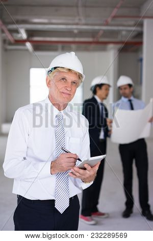 Ambitious Architect In Hardhat Viewing Building Site And Thinking Of Design. Content Foreman Writing