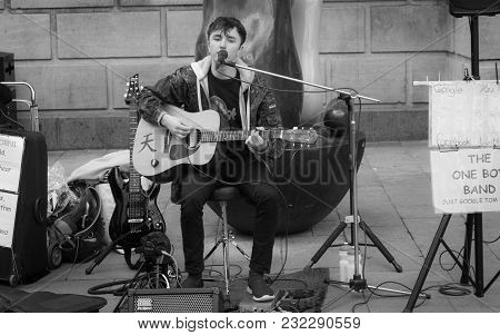 Cambridge, United Kingdom - April 17, 2016: A Teenage Boy Playing Multiple Instruments And Singing A