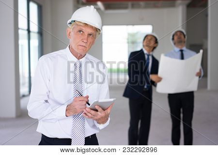 Pensive Contractor Analyzing Building Structure And Making Notes. Concentrated Senior Foreman In Wor
