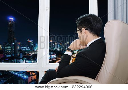 Side View Of Young Handsome Business Man With Eyeglasses Sitting On Sofa Chair In Modern Office With