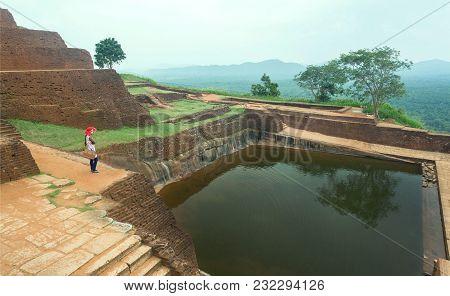 Sigiriya, Sri Lanka - Jan 9, 2018: Lonely Woman Watching Ruins Of The Ancient Sigiriya City With Wat