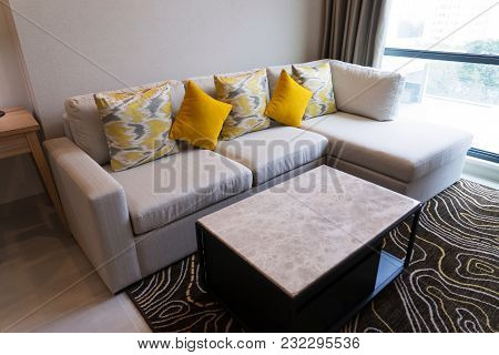 Comfortable Corner Sofa With Fashioned Cushions And Coffee Table On Carpet In Living Room. Furniture