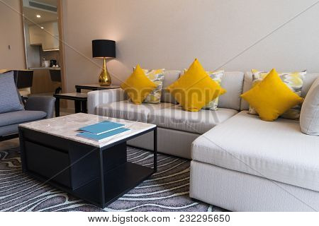 Cushioned Corner Sofa And Coffee Table In Living Room. Modern Comfortable Furniture With Carpet. Hot