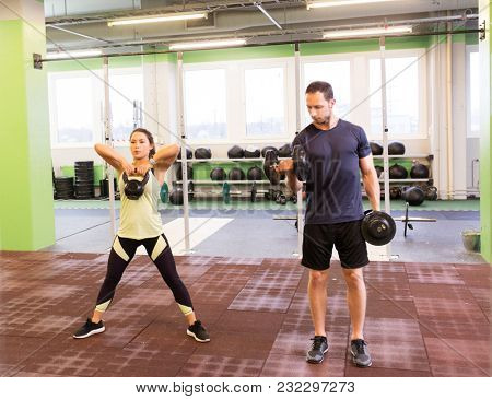 sport, fitness, lifestyle and people concept - woman with kettlebell and man with dumbbell exercising in gym
