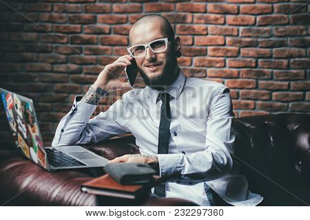 Young brutal businessman is working at home using his laptop and smartphone. Male beauty, fashion. Business concept. Modern technologies.