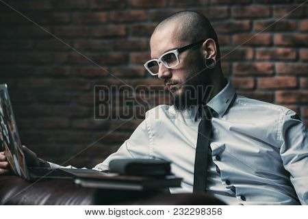 Young brutal businessman is working at home using his laptop. Male beauty, fashion. Business concept. Modern technologies.