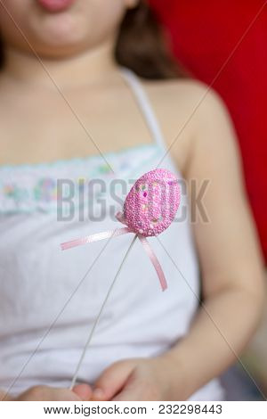 Little Kid Girl Holding Easter Egg On A Stick In A Hand
