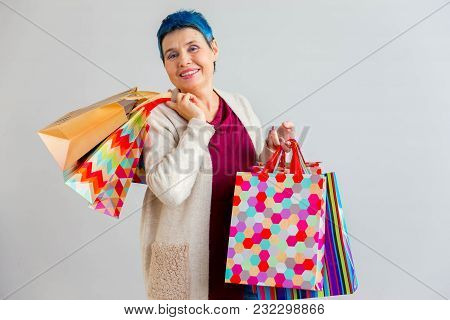A Portrait Of A Senior Woman With Shopping Bags