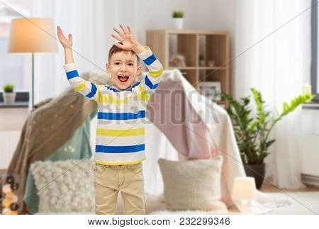 childhood, fashion, joy and people concept - happy little boy waving hands at home over kids room and tepee background