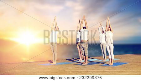 yoga and healthy lifestyle concept - group of people doing upward salute pose on wooden pier over sea background