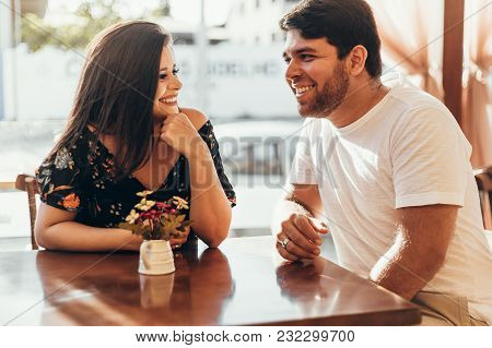 Young Couple In Love Sitting In A Cafe, Having A Conversation And Enjoying The Time Spent With Each