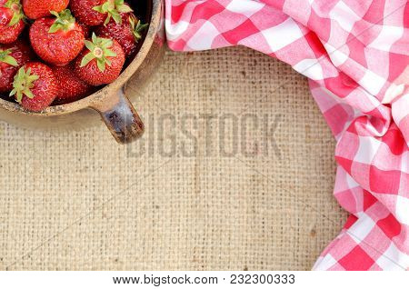 Half Of Old Ceramic Pot Full Of Fresh Red Strawberries On Canvas And Red Checkered Rural Tablecloth.