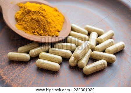 Natural Herb Food Supplement Turmeric Veggie Capsules And Spoon With Orange Curcumin Powder On Clay