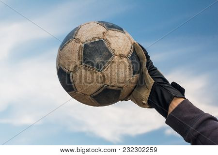 Football Goalkeeper Catching Soccer Old Ball On Blue Sky With Clouds
