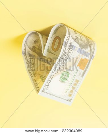 Hundred Dollar Bill In Heart Shape On Yellow Background