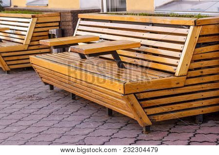 A Wooden Bench With Tables On A Stone Pavement.