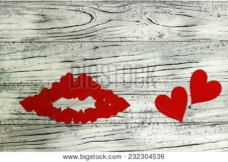 Lips Of Little Red Hearts On A Wooden Background. The Concept Of Valentine's Day.