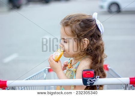 Little Girl Eating A Donut At Mall Parking