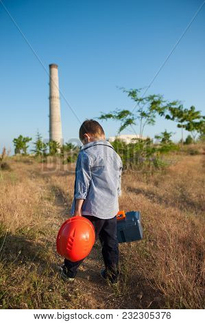 Sad Little Boy With Helmet And Tool Case In Hands Walking Towards Factory With Pipe