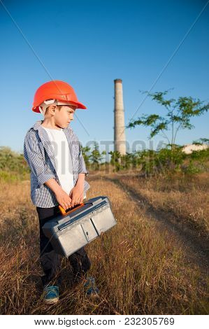 Handsome Little Kid In Orange Helmet With Tool Case In Hands Near Old Factory With High Pipe