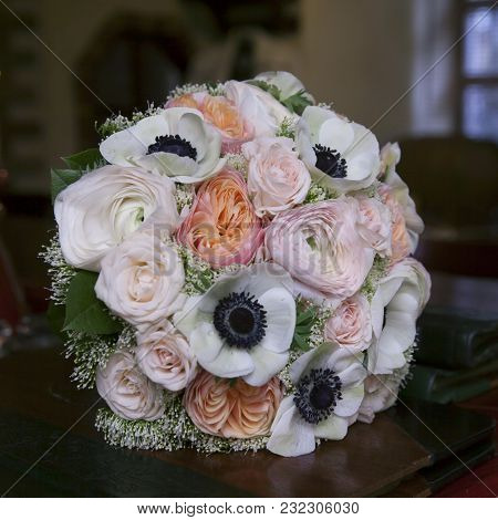 Bride Holds Wedding Bouquet Of Pink Roses And White Anemone And Pink Ranunculus Lying On Wooden Floo