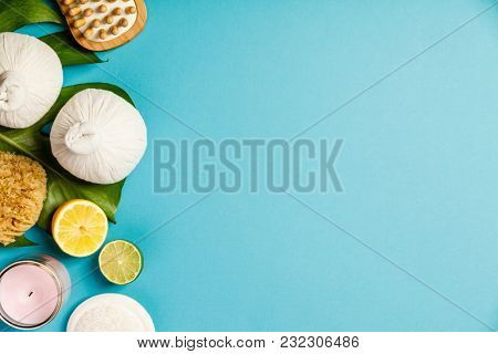 Spa massage compress balls, candle, towel, fruits and leaves on blue background. Top view, flat lay, copyspace