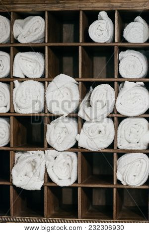 Freshly Laundered Fluffy Towel Rolls On A Wooden Commode. Welcome Resort Decor In Slow Motion. Top Q