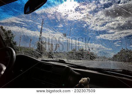 Road View Through Car Window Blurry With Heavy Rain, Driving In Rain, Rainy Weather. Rainy Sunny Wea