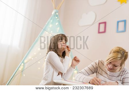 Mother And Daughter Drawing With Crayons; Daughter Putting The Crayon Make-up On