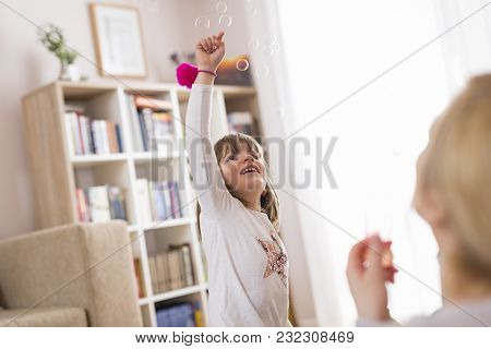 Mother And Daughter Playing, Making Soap Bubbles And Having Fun