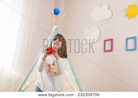 Beautiful Little Girl Playing In Her Room, Practising Juggling And Having Fun