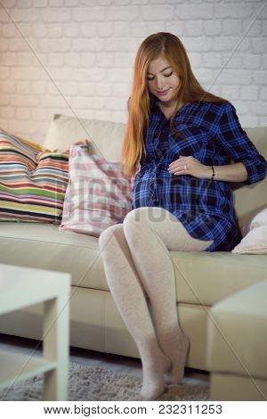 Beautiful red-haired young pregnant woman sitting at home on the couch and looking out the window stroking her belly with a baby.