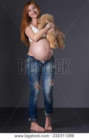 Beautiful red-haired pregnant woman in top and jeans on a gray background