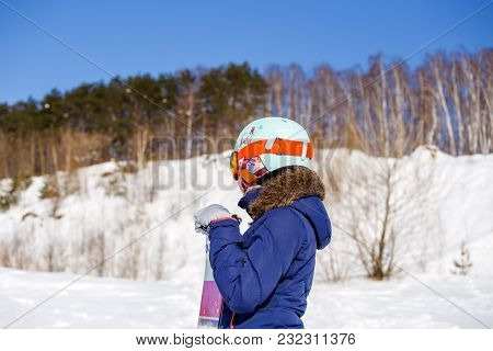 Photo Of Side View Of Sporty Woman In Helmet With Snowboard Looking At Camera In Winter Day