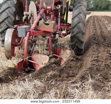 A Vintage Tractor Ploughing A Straight Line Furrow.