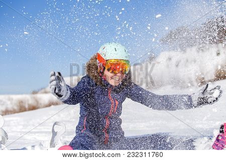 Picture Of Athlete Woman Sitting In Snowdrift , Throws Snow In Winter