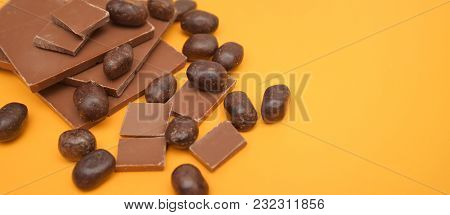 Chocolate Bar And Chocolate Pieces Over Yellow Background. Sweet Dessert.